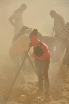 Egipscy robotnicy w tumanach pyłu usuwają skalny rumosz i trap z półki skalnej..., fot. Sławomir W. Malinowski